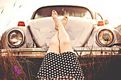 Caucasian teenage girl resting feet on vintage car