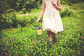 Girl picking flowers in rural field