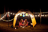 Girls relaxing in camping tent at night