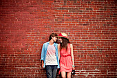 Couple leaning on brick wall