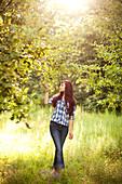 Girl admiring trees in rural field