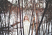 Caucasian girl playing in snowy forest