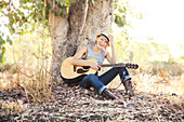 Caucasian musician holding guitar under tree