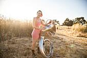 Caucasian musician carrying tuba on dirt path
