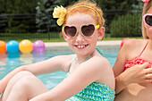 Caucasian girls smiling near swimming pool