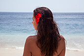 Rear view of woman wearing flower in her hair on beach