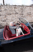 Older woman driving convertible with dog