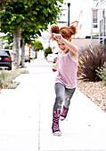 Smiling girl running on city sidewalk