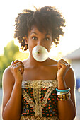 Woman blowing bubble gum bubble outdoors