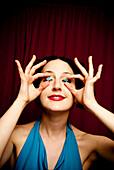 Glamorous woman holding stars over eyes