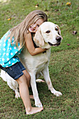 Smiling girl hugging dog in field