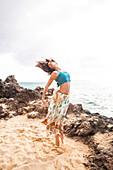 Woman dancing on rocky beach