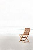 Empty folding chair on beach