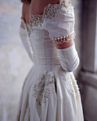 Close up of bride wearing wedding gown