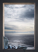 Knitted scarf in window over seascape