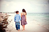 Brother and sister walking on beach