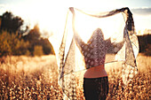 Woman playing with scarf in rural field