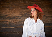 Teenage girl wearing cowboy hat by wooden wall
