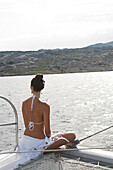 Woman admiring ocean from sailboat deck