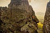 Caucasian hiker climbing on rock formation