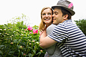 Caucasian man hugging girlfriend in garden