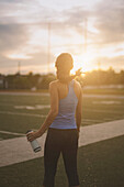 Mixed race athlete holding water bottle on sports field