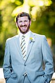Caucasian groom laughing in garden