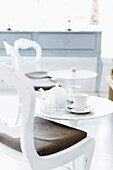 Cafe table with cups of coffee and coffee pot