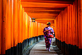 Woman in kimono walking under wooden pillars
