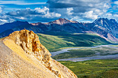 A couple sitting on a rock ledge taking in the view at Polychrome Pass in Denali National Park, Interior Alaska