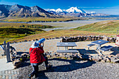 A male visitor views Mt. McKinley through the park provided scope at Eielson Visitor Center in Denali National Park, Interior Alaska, Summer, USA.