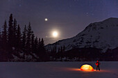 Nighttime view of a man standing next to a lit tent on a snow covered Trail Lake with the moon, stars, and planets overhead, Moose Pass, Kenai Peninsula, Southcentral Alaska