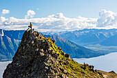 Female hiker stands on a rocky outcrop along Bird Ridge trail overlooking Turnagain Arm and the Kenai Mountains, Southcentral Alaska