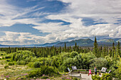 Mother and daughter view scenery from a platform along the Alaska Highway south of Kluane Lake, Yukon Territory, Canada, summer