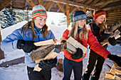 Three Young Women Collect And Pile Chopped Wood Near Homer, Alaska During Winter.
