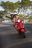 Young couple riding a red scooter on a coastal road along the Cap de Formentor peninsula, Palma, Mallorca, Balearic Islands, Spain