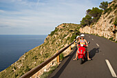 Young couple riding a red Vespa scooter on a coastal road along the Cap de Formentor peninsula, Palma, Mallorca, Balearic Islands, Spain