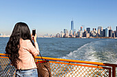 Asian woman with taking pictures with her cellphone, mobile phone, Ferry to Staten Island, view over the Hudson to downtown Manhattan and the new  One World Trade Center, New York City, USA, America