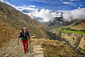 Young woman, hiker, trekker in the surreal landscape typical for Mustang in the high desert around the Kali Gandaki valley, the deepest valley in the world. Fertile fields are only possible in the high desert due to a elaborate irrigation system. In the b