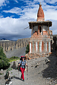 Young woman, trekker walking in front of a Buddhist stupa, Tangge, tibetian village with a buddhist Gompa in the Kali Gandaki valley, the deepest valley in the world, Mustang, Nepal, Himalaya, Asia