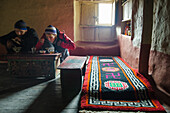 Young man and young woman eating in a typical tibetan living room, house in Lupra, small village with a buddhist Gompa at the Kali Gandaki valley, the deepest valley in the world, Mustang, Nepal, Himalaya, Asia