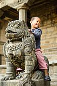 Small girl on a stone sculpture in Kathmandu, Nepal, Himalaya, Asia