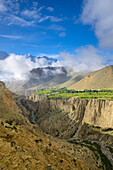 Surreal landscape typical for Mustang in the high desert around the Kali Gandaki valley, the deepest valley in the world. Fertile fields are only possible in the high desert due to a elaborate irrigation system. In the background the Gurung village Ghyaka