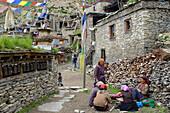 Prayer wheels, prayer flags and tibetan women in Nar on the Nar Phu Trek, Nepal, Himalaya, Asia
