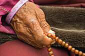 Buddhist monch praying with his prayer beads Mala consisting of 108 beads, representing the 108 volumes of Buddha's lessons, Nar, on the Nar Phu Trek, Nepal, Himalaya, Asia