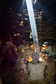 Yak shepherds from Nar in their summer residence at the camp fire, sun beam, light beam illuminates the smoke of the campfire, Nepal, Himalaya, Asia