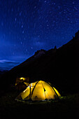 Bright luminescent tent beneath the star carousel in the High Camp on the way from Nar over Teri La to Mustang, Nepal, Himalaya, Asia