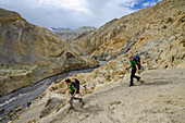 Young men, hikers, trekkers in the surreal landscape typical for Mustang in the high desert around the Kali Gandaki valley, the deepest valley in the world, Mustang, Nepal, Himalaya, Asia
