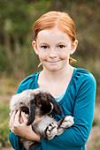 Girl carrying rabbit outdoors