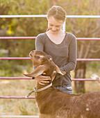 Smiling girl hugging goat on farm